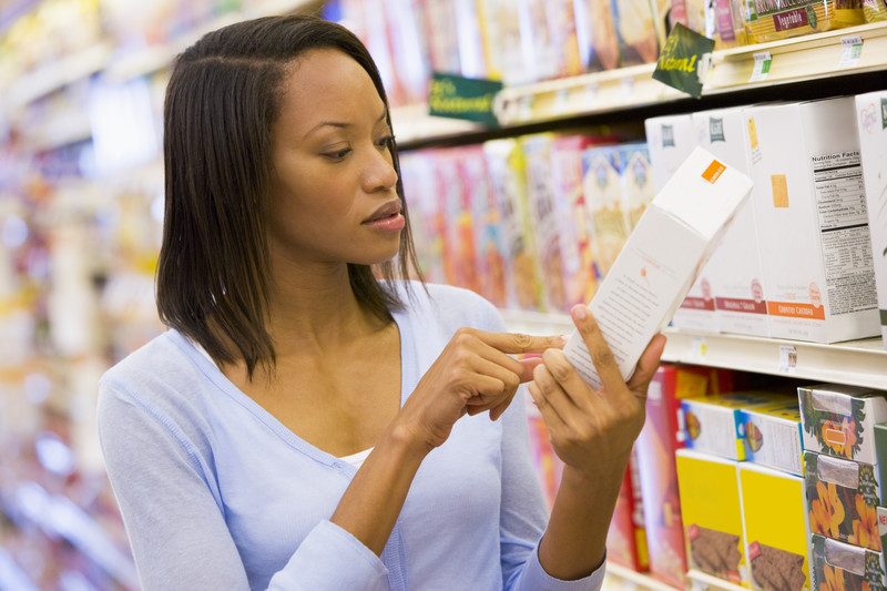 Woman in a grocery store reading the food label on a package