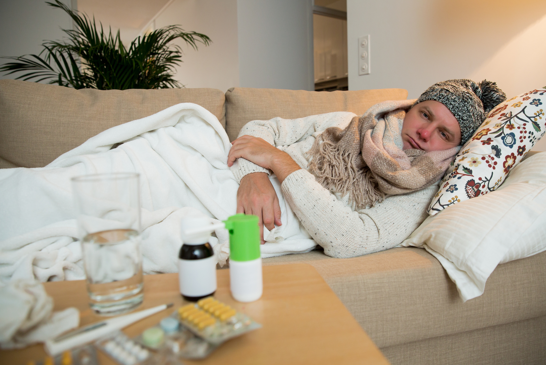 Sick man lying on couch under a blanket checking temperature. Living room with table full of medicines.