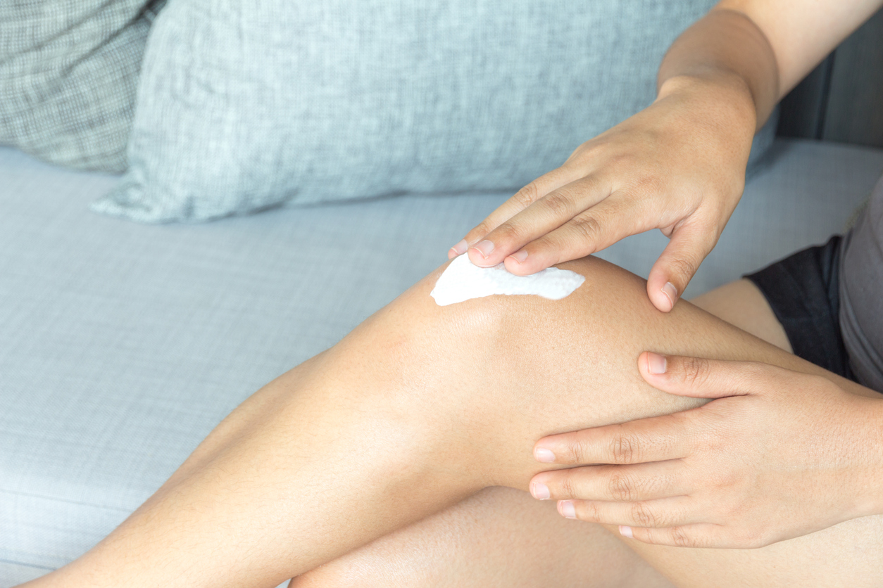 woman applying moisturizer to dry skin on her leg