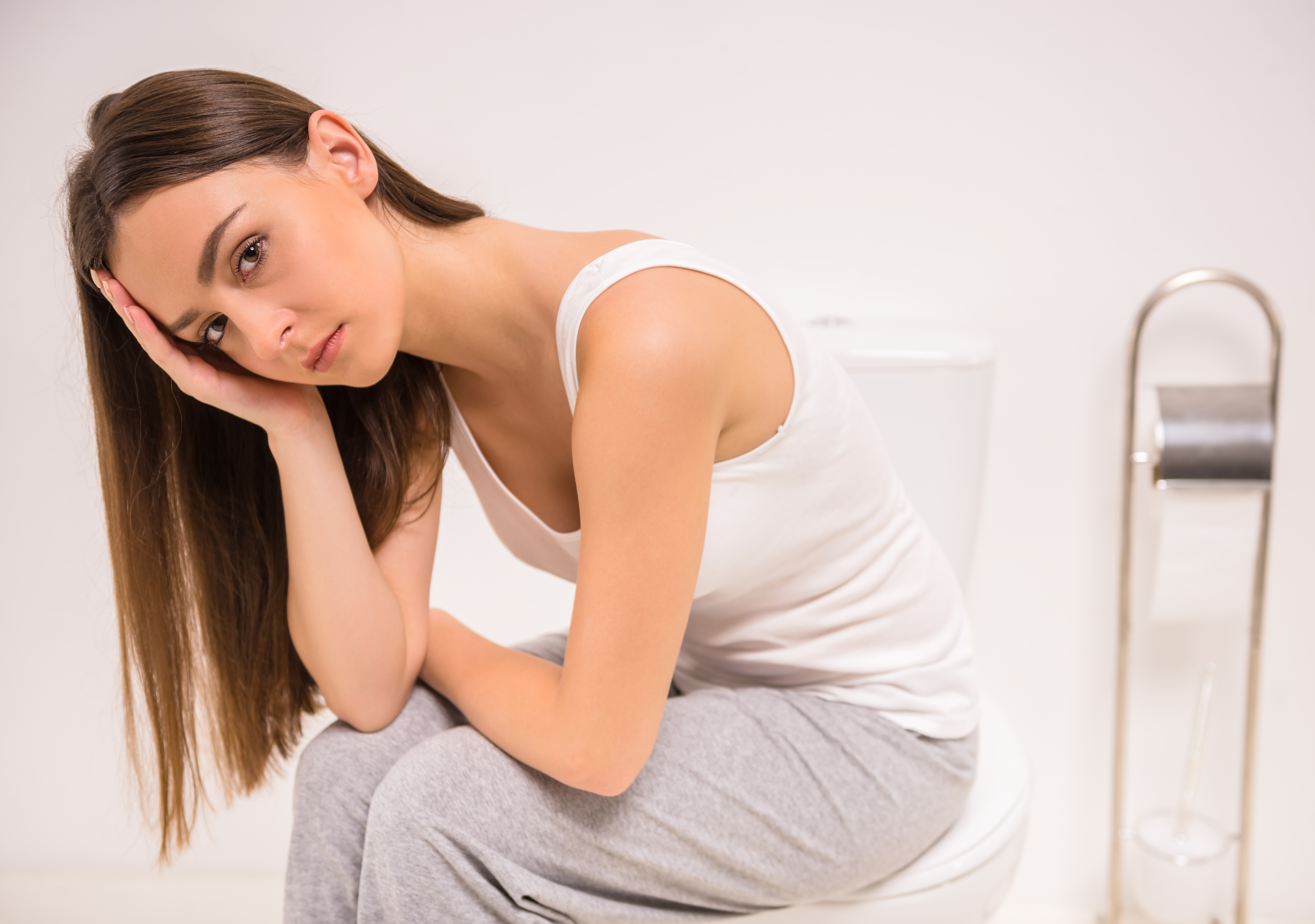 Young woman on toilet, looks unhappy