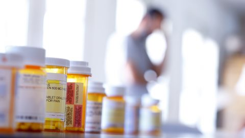 A large group of medicines in foreground, man in pain in background