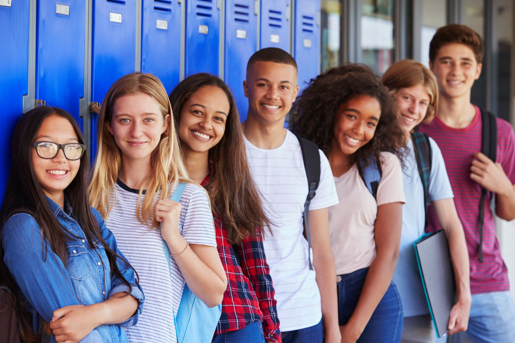 A group of teens standing next to lockers in school