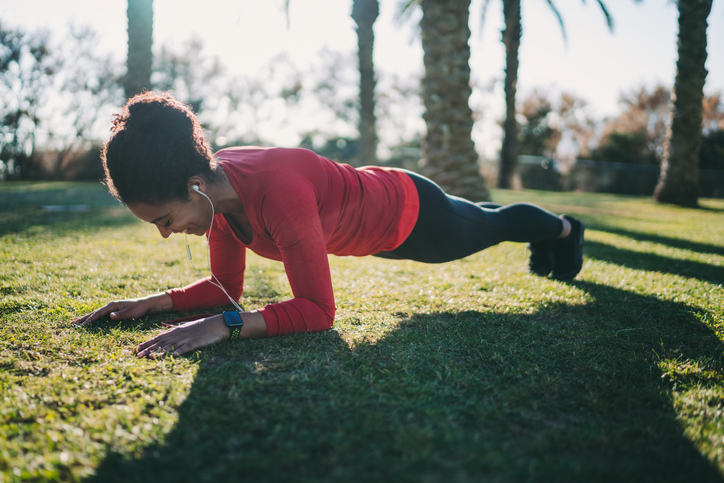 A woman holding a plank position in a park