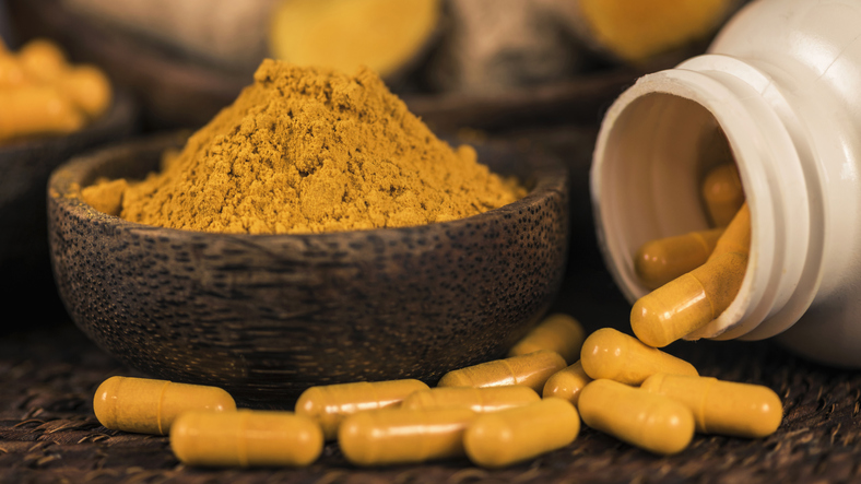 Curcumin herbal supplements and turmeric powder in bowl