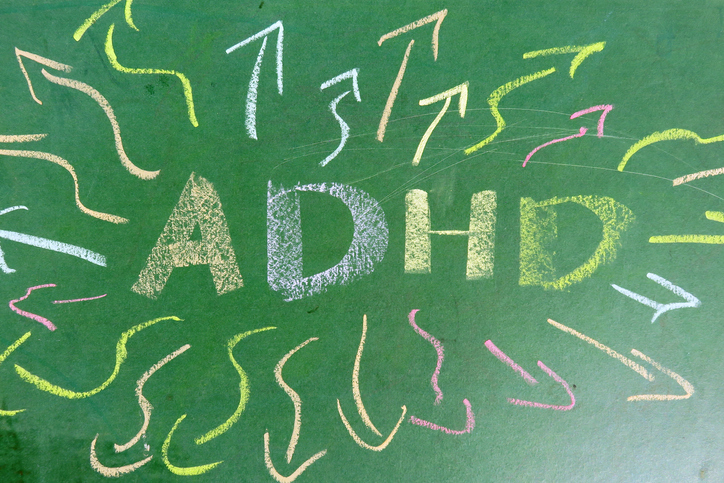 ADHD written in chalk with arrows representing thoughts going in many different directions