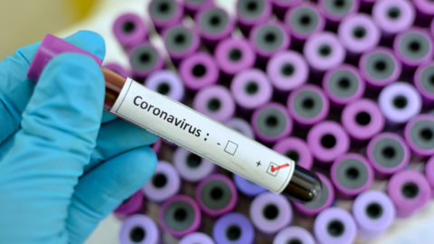 A gloved hand holding a blood sample vial marked Coronavirus positive