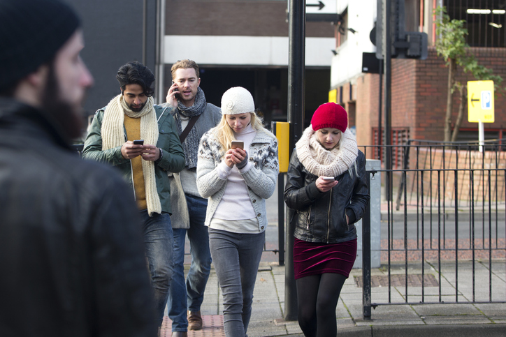 People distracted by cell phones while crossing street