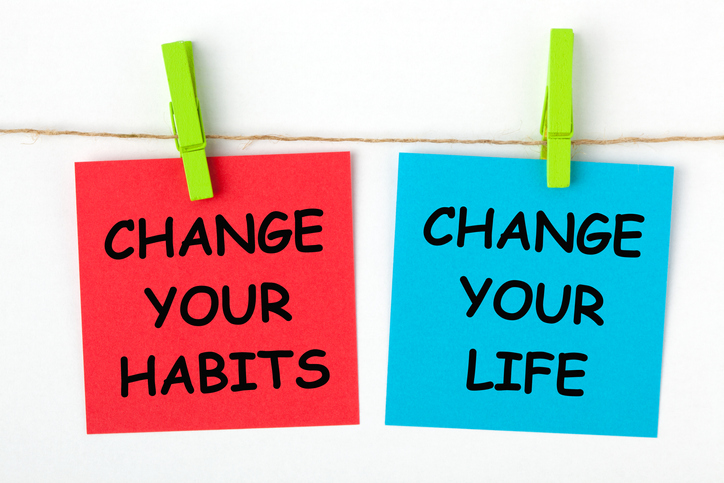 Change your habits, change your life written on color notes and hung on line with clothespins