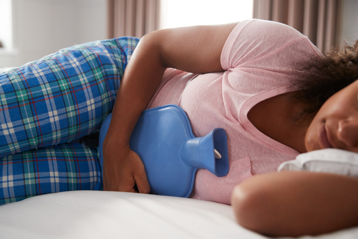 Young woman in pajamas using hot water bottle to ease period pain