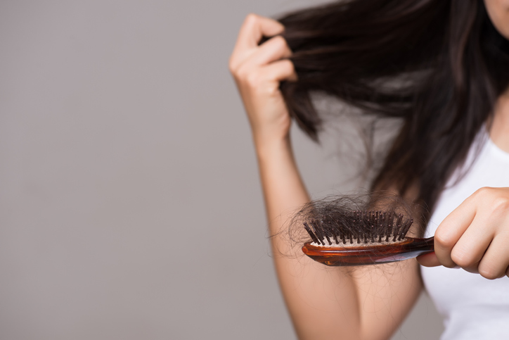 Thinning hair concept, woman showing brush holding hair that has fallen out