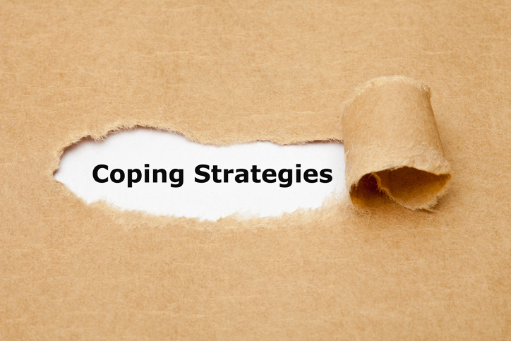 "The words ""Coping Strategies"" revealed as brown paper is torn away"