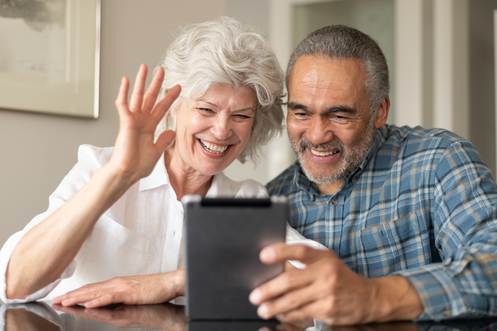 Older couple smiling, woman waving, while video chatting