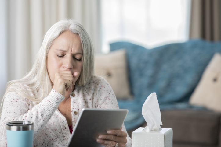 Older woman coughing during telehealth visit with a healthcare provider on her tablet