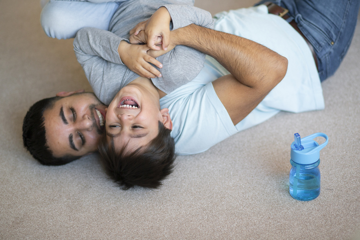 A close up of a young boy playing on the floor with his father.