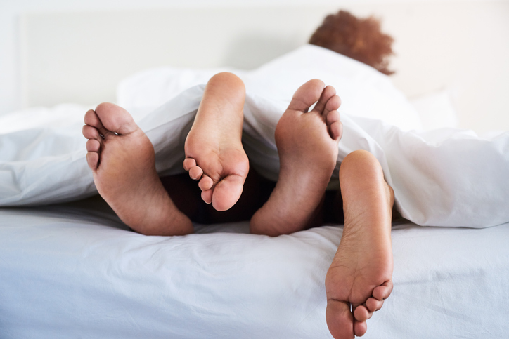 a couple's feet poking out from under the sheets