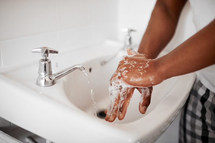 Cropped shot of man washing his hands in a sink