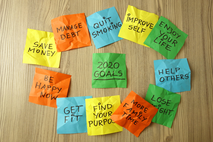 Crumpled 2020 new year resolution goals handwritten on colorful sticky notes