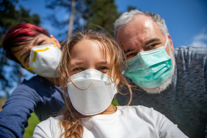 Family selfie outdoors with face masks on