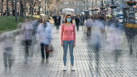 Woman wearing face mask stands at distance from blurred people walking by