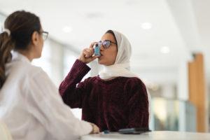 mulher usando inalador para asma