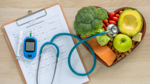 Healthy foods, glucose meter and clipboard to record readings, stethoscope as concept for managing diabetes