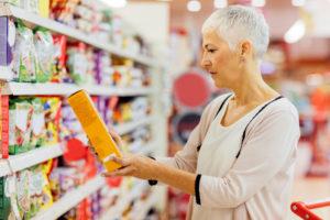 mulher verificando se há grãos inteiros no rótulo dos alimentos