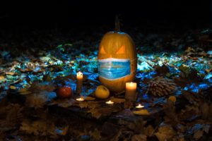 Halloween pumpkin in medical mask and candles in dark forest. Concept protected holiday halloween.