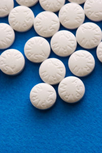 Aspirin tablets on blue background