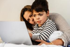 mãe e filho com necessidades especiais acessando educação especial no laptop