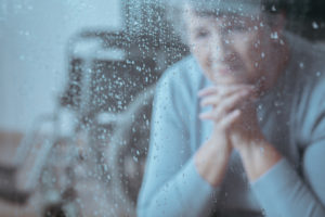 older woman at rainy window