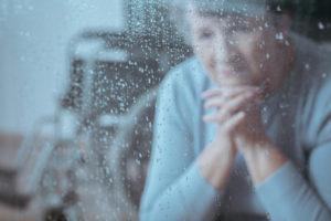 older woman at rainy window