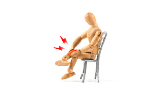 Wooden mannequin holding painful leg; concept is neuropathy burning, tingling, numbness