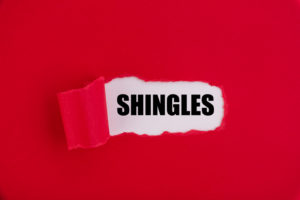"The text ""Shingles"" appearing behind torn red paper."