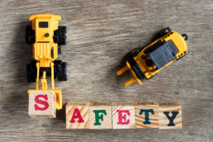 "Two yellow toy plastic bulldozers, one moving a block with the letter ""S"" to write the word ""SAFETY"" in block letters"