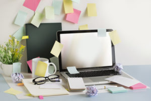 Cluttered desk top, many sticky notes, distractions; concept of ADHD, trouble focusing at work