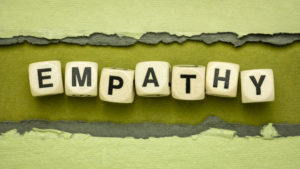 empathy word abstract in wood cubes against handmade rag paper, ability to understand and share the feelings of another