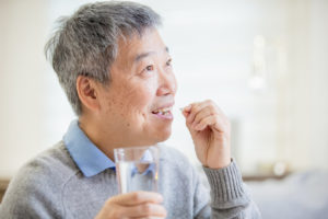 older asian man taking cholesterol medication