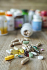 Many nutritional health supplements and vitamins in capsules, tablets on a wood background with their bottles in the background, shallow depth of focus.