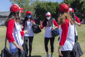 Teenage girls on baseball team wearing masks and preparing for outdoor workout