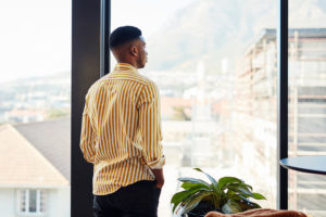 young black man looking out window