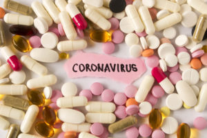 The word coronavirus on pink paper surrounded by scattered vitamins and supplements; COVID-19.