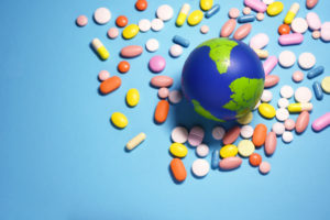 pills surrounding the earth globe on a blue background;  healthy planet concept;  Earth day
