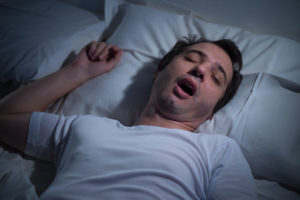 Man sleeping in his bad at night, snoring, mouth open; sleep apnea concept